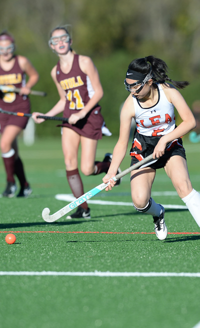 field hockey player nearing ball on the ground to hit it