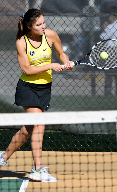 girls varsity tennis player hitting a backhand volley