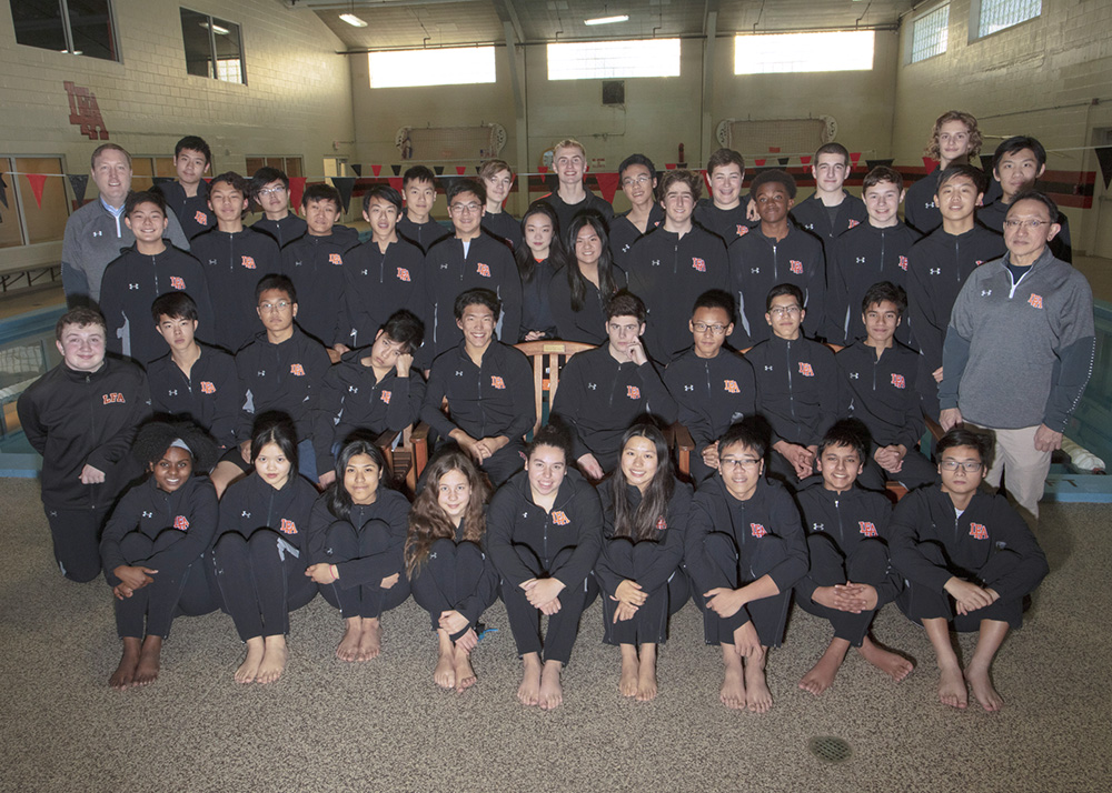 swim team pose for photo in front of pool